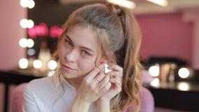 Το κορίτσι προσπαθεί στα σκουλαρίκια φιλμ μικρού μήκους