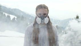 Το κορίτσι προστατεύεται από τον κακούς αέρα και τον καπνό σε μια μάσκα αερίου απόθεμα βίντεο