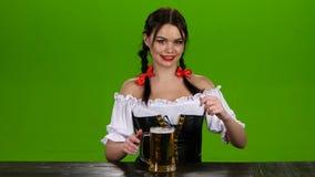 Το κορίτσι προσφέρει να δοκιμάσει την εύγευστη μπύρα στην πράσινη οθόνη Oktoberfest απόθεμα βίντεο