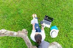 Το κορίτσι προσώπων τρόπου ζωής απολαμβάνει ένα βιβλίο και παίζει το lap-top στον τομέα χλόης του πάρκου φύσης Στοκ εικόνα με δικαίωμα ελεύθερης χρήσης