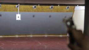 Το κορίτσι πυροβολεί ένα πυροβόλο όπλο φιλμ μικρού μήκους