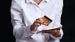 Το κορίτσι πληρώνει για μια σε απευθείας σύνδεση αγορά με μια ταμπλέτα και μια πιστωτική κάρτα μαύρα κλείστε επάνω απόθεμα βίντεο