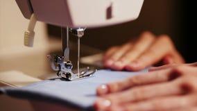 Το κορίτσι ράβει τα ενδύματα ράβοντας βελόνες ράβοντας μηχανών στις μπλε και κίτρινες κινηματογραφήσεων σε πρώτο πλάνο απόθεμα βίντεο