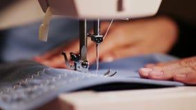 Το κορίτσι ράβει τα ενδύματα ράβοντας βελόνες ράβοντας μηχανών στις μπλε και κίτρινες κινηματογραφήσεων σε πρώτο πλάνο φιλμ μικρού μήκους