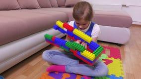 Το κορίτσι ρίχνει από το κτήριο των τούβλων παιχνιδιών απόθεμα βίντεο