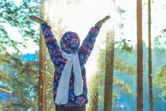 Το κορίτσι ρίχνει το χιόνι στο ηλιόλουστο χειμερινό δάσος Στοκ Εικόνες