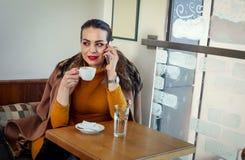 Το κορίτσι σε έναν καφέ πίνει τον καφέ και την ομιλία στο smartphone Στοκ φωτογραφία με δικαίωμα ελεύθερης χρήσης