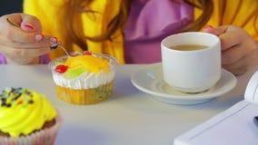 Το κορίτσι σε έναν καφέ στον πίνακα πίνει το τσάι και τρώει τα κέικ με ένα κουτάλι φιλμ μικρού μήκους