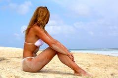 Το κορίτσι σε ένα άσπρο μπικίνι με μακρυμάλλη κάθεται σε μια παραλία άμμου στοκ φωτογραφία