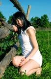 Το κορίτσι σε ένα άσπρο φόρεμα κάθεται στη χλόη Στοκ Εικόνες