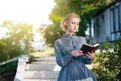 Το κορίτσι σε ένα εκλεκτής ποιότητας φόρεμα διαβάζει ένα βιβλίο Στοκ Εικόνα
