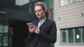 Το κορίτσι σε ένα επιχειρησιακό κοστούμι στέλνει στο κινητό τηλέφωνο Ο αέρας στην τρίχα σας φιλμ μικρού μήκους