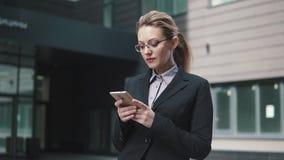 Το κορίτσι σε ένα επιχειρησιακό κοστούμι στέλνει στο κινητό τηλέφωνο Ο αέρας στην τρίχα σας απόθεμα βίντεο