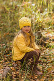 Το κορίτσι σε ένα κίτρινο σακάκι και μια κίτρινη συνεδρίαση καπέλων σε ένα δέντρο περπατούν βαριά στο δάσος φθινοπώρου μια ηλιόλο Στοκ φωτογραφίες με δικαίωμα ελεύθερης χρήσης