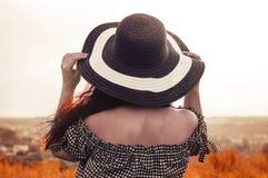 Το κορίτσι σε ένα καπέλο εξετάζει το ηλιοβασίλεμα στοκ φωτογραφίες με δικαίωμα ελεύθερης χρήσης