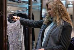 Το κορίτσι σε ένα κατάστημα ιματισμού επιλέγει το φόρεμα στοκ εικόνα με δικαίωμα ελεύθερης χρήσης