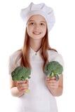Το κορίτσι σε ένα κοστούμι του μάγειρα με ένα καλάθι των λαχανικών και των φρούτων στο απομονωμένο υπόβαθρο Στοκ φωτογραφία με δικαίωμα ελεύθερης χρήσης