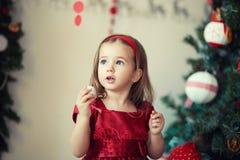 Το κορίτσι σε ένα κόκκινο ντύνει το χριστουγεννιάτικο δέντρο Στοκ φωτογραφία με δικαίωμα ελεύθερης χρήσης