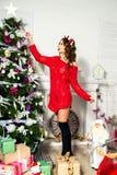 Το κορίτσι σε ένα κόκκινο πουλόβερ είναι διακοσμημένο χριστουγεννιάτικο δέντρο Νέο έτος συμπυκνωμένο Στοκ Εικόνες
