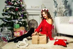 Το κορίτσι σε ένα κόκκινο πουλόβερ κάθεται κοντά σε ένα χριστουγεννιάτικο δέντρο με ένα δώρο ΝΕ Στοκ εικόνα με δικαίωμα ελεύθερης χρήσης