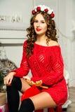 Το κορίτσι σε ένα κόκκινο πουλόβερ κάθεται σε μια άλκη παιχνιδιών Χριστούγεννα και νέο Yea Στοκ φωτογραφία με δικαίωμα ελεύθερης χρήσης