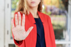 Το κορίτσι σε ένα κόκκινο σακάκι κάνει την παύση της χειρονομίας ανοικτό χέρι Στοκ Φωτογραφία