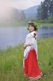 Το κορίτσι σε ένα κόκκινο φόρεμα και ένα μαντίλι στους ώμους στοκ φωτογραφία