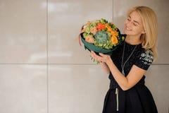 Το κορίτσι σε ένα μαύρο φόρεμα με μια ανθοδέσμη του φθινοπώρου Στοκ Εικόνες