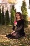 Το κορίτσι σε ένα μαύρο φόρεμα με το κόκκινο μήλο Στοκ εικόνα με δικαίωμα ελεύθερης χρήσης