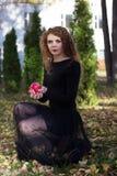 Το κορίτσι σε ένα μαύρο φόρεμα με το κόκκινο μήλο Στοκ εικόνες με δικαίωμα ελεύθερης χρήσης