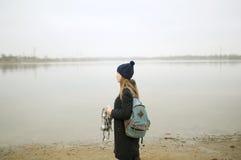Το κορίτσι σε ένα μπλε παλτό περπατά κατά μήκος του ποταμού Στοκ Εικόνες