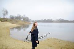Το κορίτσι σε ένα μπλε παλτό περπατά κατά μήκος του ποταμού Στοκ εικόνα με δικαίωμα ελεύθερης χρήσης