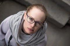 Το κορίτσι σε ένα παλτό εξετάζει τη κάμερα Στοκ Εικόνες
