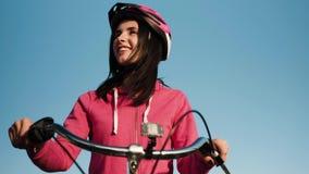 Το κορίτσι σε ένα ποδήλατο έντυσε sportswear και ένα προστατευτικό κράνος ενάντια στο μπλε ουρανό απόθεμα βίντεο