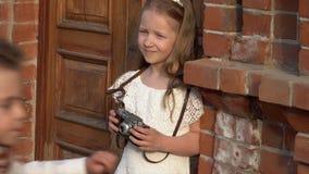 Το κορίτσι σε ένα ρόδινο φόρεμα εξετάζει την παλαιά κάμερα στα χέρια φιλμ μικρού μήκους