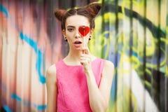 Το κορίτσι σε ένα ρόδινο φόρεμα με την καραμέλα σε ένα διακοσμημένο υπόβαθρο του τοίχου γκράφιτι Στοκ Φωτογραφία