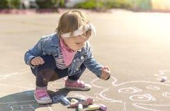 Το κορίτσι σε ένα σακάκι τζιν σύρει με τις χρωματισμένες κιμωλίες Στοκ Φωτογραφίες