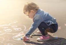 Το κορίτσι σε ένα σακάκι τζιν σύρει με τις χρωματισμένες κιμωλίες Στοκ φωτογραφία με δικαίωμα ελεύθερης χρήσης