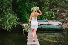 Το κορίτσι σε ένα στεφάνι με μια ανθοδέσμη να σταθεί πίσω σε μια ξύλινη γέφυρα Στοκ φωτογραφία με δικαίωμα ελεύθερης χρήσης