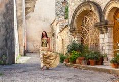 Το κορίτσι σε ένα όμορφο ξυπόλυτο περπάτημα φορεμάτων στην πόλη στοκ εικόνες