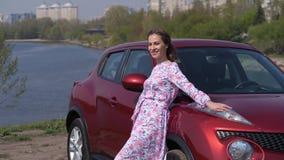 Το κορίτσι σε μια διάθεση χορού περπατά κατά μήκος του νέου αυτοκινήτου, περιστρέφει και κλίνει στην κουκούλα r φιλμ μικρού μήκους