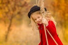 Το κορίτσι σε μια κόκκινη ταλάντευση παλτών σε μια ταλάντευση και κάνει τα αστεία πρόσωπα στοκ φωτογραφίες