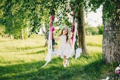 Το κορίτσι σε μια ταλάντευση διακόσμησε με τις κορδέλλες και τα λουλούδια στη φύση μια ηλιόλουστη θερινή ημέρα Στοκ Φωτογραφία
