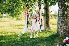Το κορίτσι σε μια ταλάντευση διακόσμησε με τις κορδέλλες και τα λουλούδια στη φύση μια ηλιόλουστη θερινή ημέρα Στοκ Εικόνες