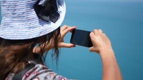 Το κορίτσι σε μια όμορφη μπλε μπλε θάλασσα καπέλων fotografiruet άνωθεν HD, 1920x1080 κίνηση αργή φιλμ μικρού μήκους