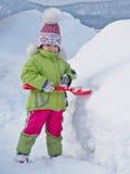 Το κορίτσι σκάβει να φτυαρίσει το χιόνι και χαμογελά στοκ φωτογραφίες