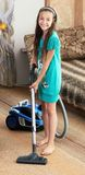 Το κορίτσι σκουπίζει με ηλεκτρική σκούπα Στοκ εικόνα με δικαίωμα ελεύθερης χρήσης