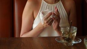 Το κορίτσι σκουπίζει τα χέρια της με μια υγρή πετσέτα πριν από το τσάι στον καφέ 4K Σε αργή κίνηση πυροβολισμός απόθεμα βίντεο