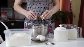Το κορίτσι σπάζει το αυγό και προσθέτει στο κύπελλο του αλευριού, αναμιγνύοντας όλα τα συστατικά απόθεμα βίντεο