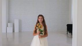 Το κορίτσι στέκεται και κοιτάζει στο πλαίσιο στην άσπρη σοφίτα φιλμ μικρού μήκους